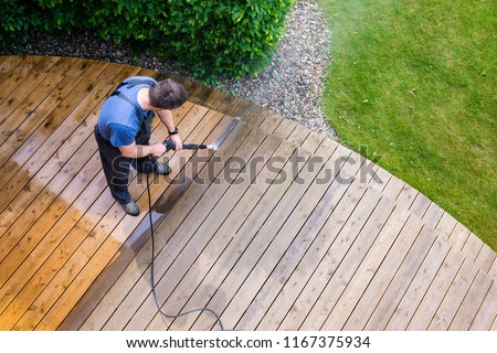 man cleaning terrace with a power washer - high water pressure cleaner on wooden terrace surface #1167375934