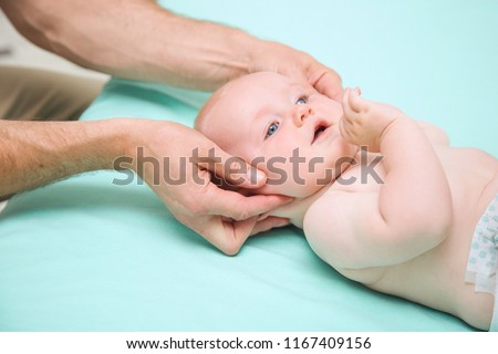 Seven month baby boy head being manipulated by osteopathic manual therapist or physician #1167409156