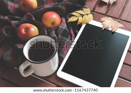 Tablet hot tea checkered blanket apples and autumn leaves on old wooden background Vintage tonning Autumn concept mock up