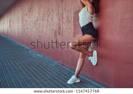 Cropped photo of a beautiful girl dressed in shorts and t-shirt posing on a camera while leaning on wall at sidewalk under the bridge. #1167457768