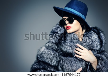 Beautiful woman in luxurious fur coat posing in studio. Luxury, rich lifestyle. Fashion shot.  #1167544177