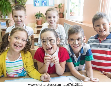 portrait of a group of primary school children in a class at their desks #1167612811