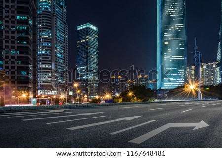 empty pavement and modern buildings in city in night #1167648481