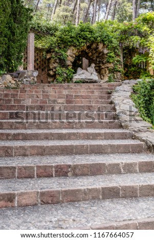 Barcelona, Spain - May 10, 2018: Stone stairs leading to the grotto of the nymph Egeria built by Bagutti in 1804 in Horta Labirinth Park. The sculpture of a sleeping nymph is made of white marble. #1167664057