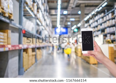 Hands holding mobile phone with shopping mall or department store  blurred background and bokeh light #1167666154
