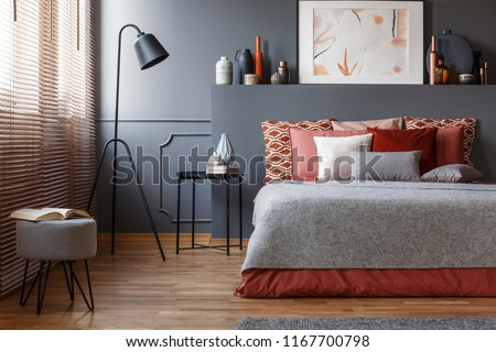 Stool and lamp near bed with pink and grey bedding in bedroom interior with poster on headboard #1167700798