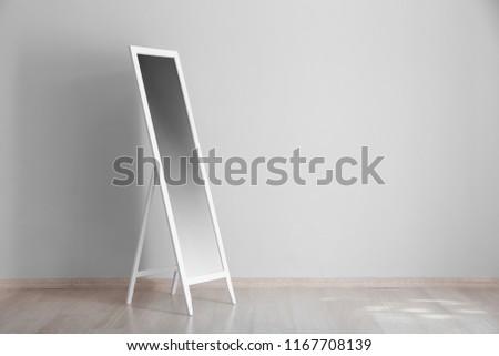 Big stylish mirror near light wall in empty room #1167708139