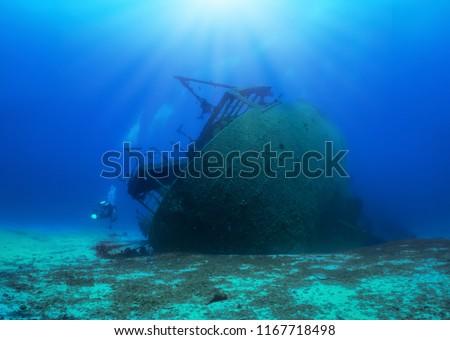 A sunken shipwreck in the mediterranean sea with a scuba diver, Greece #1167718498