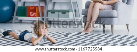 Panorama of bored autistic boy on carpet during meeting with psychotherapist #1167725584
