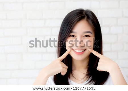 Portrait of beautiful young asian woman happiness standing finger touch cheek on gray cement texture grunge wall brick background, businesswoman is a smiling on concrete, business people concept. #1167771535