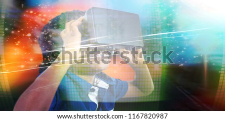 Boy wearing virtual reality simulator  against glittering screen in urban setting #1167820987