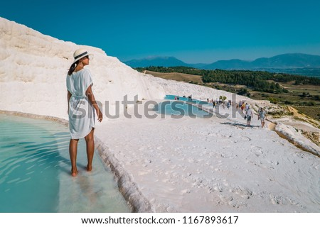 Natural travertine pools and terraces in Pamukkale. Cotton castle in southwestern Turkey, girl in white dress with hat natural pool Pamukkale #1167893617