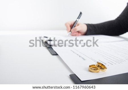 Hands of wife, husband signing decree of divorce, dissolution, canceling marriage, legal separation documents, filing divorce papers or premarital agreement prepared by lawyer. Wedding ring #1167960643