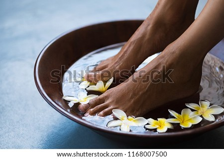 Woman soaking feet in bowl of water with floating frangipani flowers at spa. Closeup of a female feet at wellness center on pedicure procedure. Woman feet in spa wooden bowl with exotic white flowers. #1168007500