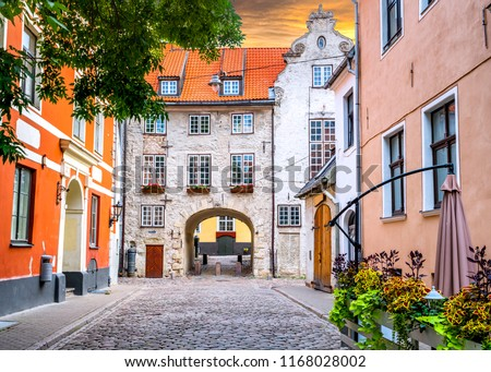 Medieval street in old Riga, Latvia, Europe. In old Riga tourists can find unique medieval architectural ensembles and ancient buildings #1168028002