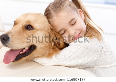 Cute little girl hugging golden retriever with love eyes closed, smiling. #116807197