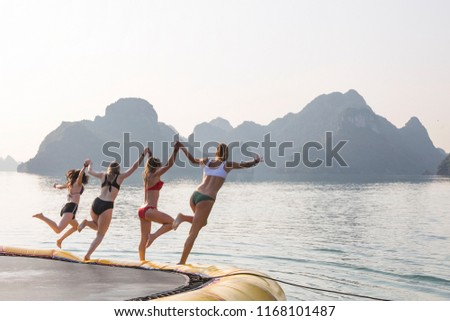 Four girls in bikini's jump off a platform into water whilst holding hands. They are In Vietnam's Halong Bay, and limestone mountains are visible in the background. #1168101487