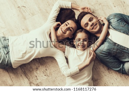 Happy Family Lying of Floor Together at Home. Beautiful Woman Handsome Man and Adorable Little Girl Lying on Parquet Floor and Hugging. Parents and Child Together. Family and Parenthood Concept #1168117276