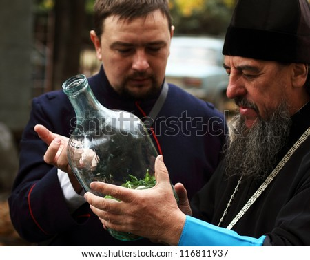 LUGANSK - OCT 14: Don Cossack  tells Orthodox priest about ancient cooking utensil vodka infusions, celebration of the Protection of the Mother of God, Lugansk, Ukraine, October 14, 2012 #116811937