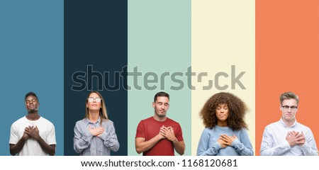 Group of people over vintage colors background smiling with hands on chest with closed eyes and grateful gesture on face. Health concept. #1168120681