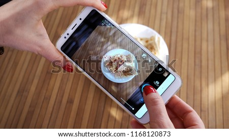 The girl takes a photo of the plate with Gözleme. The blogger uses a cell phone to photograph food in a Turkish hotel. Concept photo for social network.