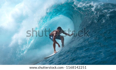 CLOSE UP Crystal clear water splashes over surfer riding an epic barrel wave in spectacular Tahiti. Extreme pro sportsman surfing a breathtaking emerald wave on a perfect sunny day in French Polynesia #1168142251