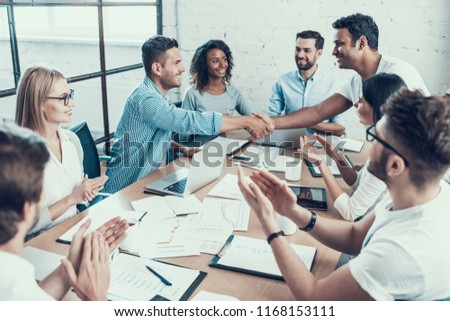 Successful Business Team Congratulating Colleague. Group of Young Happy Collegues Celebrating in Modern Office. Creative Successful Team at Work. Teamwork Concept. Corporate Lifestyle #1168153111