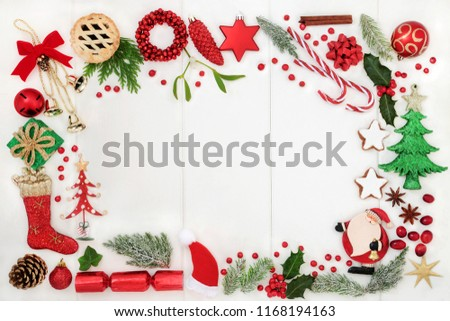 Christmas background border with traditional symbols of bauble decorations, candy canes, mince pies, fruit, spices and winter flora on rustic white wood. Top view. #1168194163
