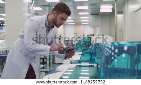 Man flips on the tablet near laboratory machine #1168259752