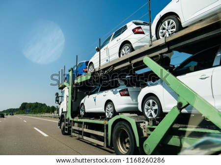 View of lgeneric white long truck trailer transporting new cars and riding on highway in sunlight under blue sky #1168260286