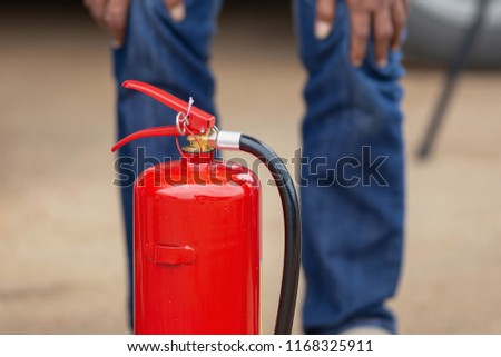 Instructor showing how to use a fire extinguisher on a training fire. #1168325911