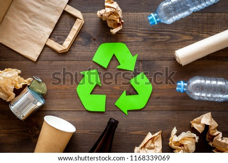 Recycling. Green recycle eco symbol. Recycled arrows sign near matherials for recycle and reuse on dark wooden background top view #1168339069