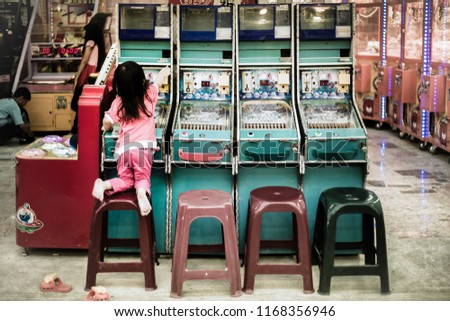 A young playful curious girl climbs on top of a chair trying to reach the top of the pinball arcade machine. She wants to insert a coin to play the game. Royalty-Free Stock Photo #1168356946