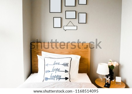 Small cozy white single condominium bedroom. Wooden twin bed, white pillow sheet, minimal furniture. Light bed lamp on small table bedside, blank white frame for putting picture hanging on wall.