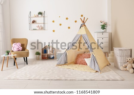 Cozy kids room interior with play tent and toys #1168541809