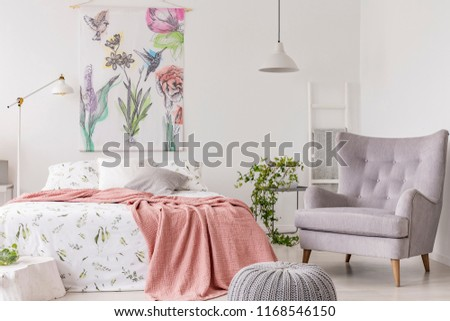 A sunny bedroom interior with a bed dressed in green pattern white linen and a peach blanket. Gray comfortable armchair beside the bed and a textile print of flowers and birds above. Real photo.
