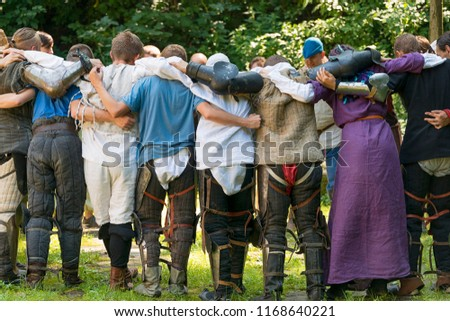 Lviv , Ukraine – august , 04, 2018:  Festival of medieval history and knight duels in the city park in Lviv. A group of participants meditating before the fight #1168640221
