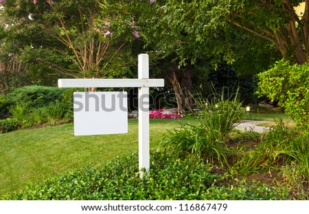 Blank white For Sale sign in well manicured yard