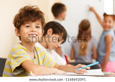 Side view of two little pupils sitting together at table and writing in copybook, one looking and smiling at camera. Smart classmates in process of learning new material in classroom. Royalty-Free Stock Photo #1168692091
