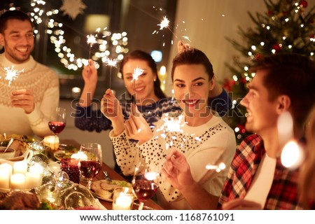 winter holidays and people concept - happy friends with sparklers celebrating christmas at home feast #1168761091