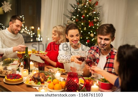 holidays and celebration concept - happy friends having christmas dinner at home, drinking red wine and clinking glasses #1168761103