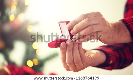 holidays, engagement and proposal concept - close up of male hands opening gift box with diamond ring for christmas #1168764199
