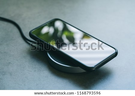 smartphone wireless charging on induction charger. Wireless charger #1168793596
