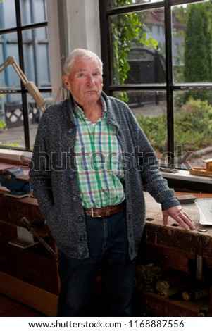 attractive male senior with checkered shirt, cardigan and jeans stands at the window of a workshop in sunlight, the outlook is sunny and green, he looks very satisfied and proud #1168887556
