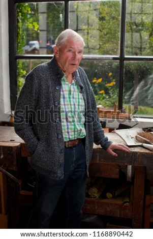 elderly man with white hair and blue eyes in leisure wear with grey cardigan, checkered shirt and jeans stands on the window of his workshop in front of sunny green background, he looks a bit tired #1168890442