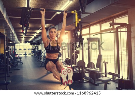 Young sportswoman lifting up on horizontal bar in gym #1168962415