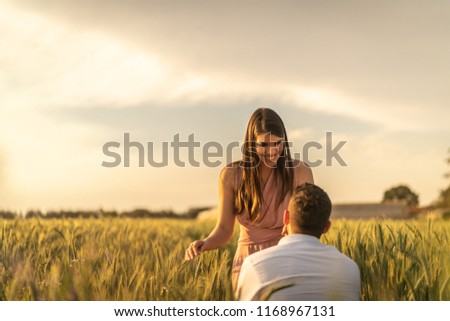 Will you marry me? Men making proposal for his girlfriend at gold wheat field  #1168967131