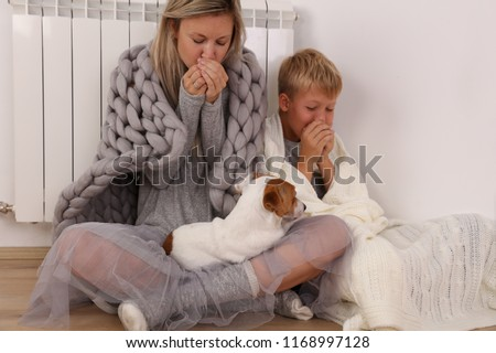 Cold home, freezing family, mother and son, Wrapped In Blanket Sitting Near Heater Royalty-Free Stock Photo #1168997128