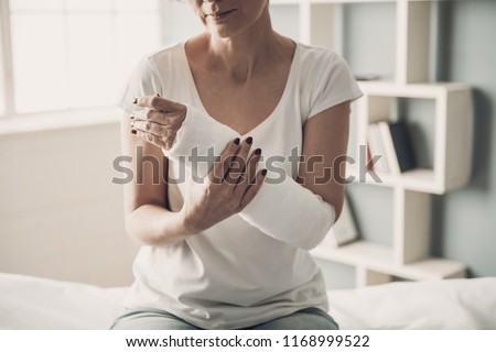 Close-up of Female Broken Arm in Plaster Cast. Caucasian Injured Woman in White T-Shirt Sitting and Holding Wrist in Gypsum Bandage with Physical Pain in Fractured Bone. Health Care concept #1168999522