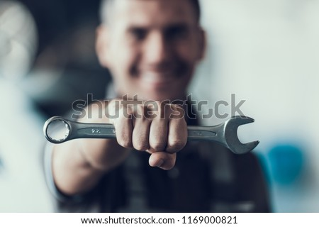 Auto Mechanic with Tool on Blurred Background. Close-up of Repairman Strong Fist Holding Metalic Wrench in Garage. Automobile Repair Service Concept. Automobile Master Concept #1169000821